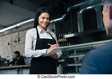 Female waiter in apron writing order - Happy female waiter...