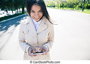 Happy woman using smartphone - Happy woman walking and using...