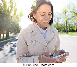 Smiling woman using smartphone - Smiling woman walking and...