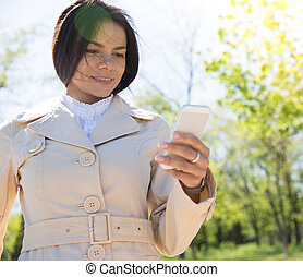 Happy woman using smartphone - Happy cute woman using...