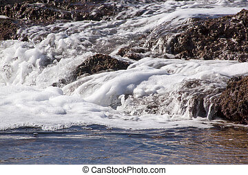 White Foaming Water Streaming over Seaweed Covered Rocks -...
