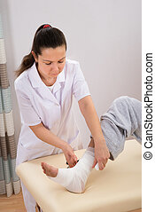 Nurse Tying Bandage On Mans Foot - Young Nurse Tying Bandage...