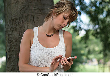Attractive blonde young woman outdoors using cell phone,...