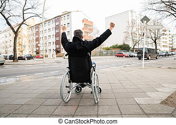 Disabled Man On Wheelchair With Hand Raised
