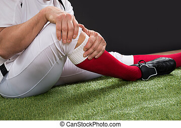 American Football Player With Injury In Leg - Close-up Of A...