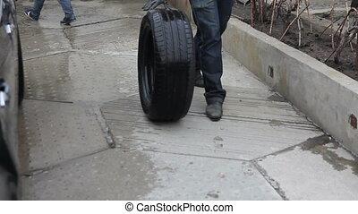 technician rolls the tire from the car to seal 01 -...