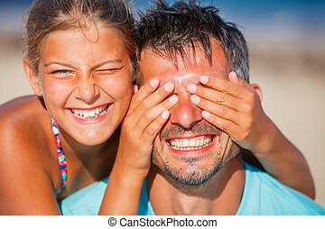 Girl  with father playing at the beach