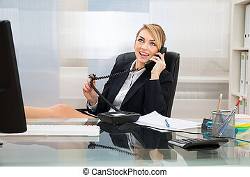 Businesswoman Talking On Landline Phone - Young Happy...