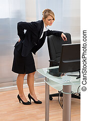 Businesswoman Having Backpain In Office - Young...