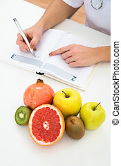 Dietician Writing Prescription With Fruits On Desk - High...