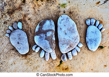 Stone footprints - Four stone footprints in the sandy beach
