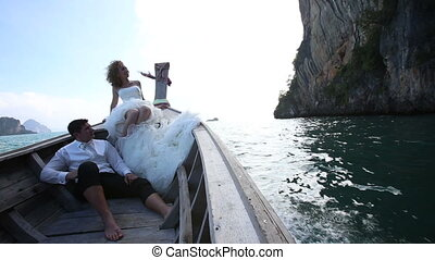 groom and blonde bride drift in longtail boat to islands -...