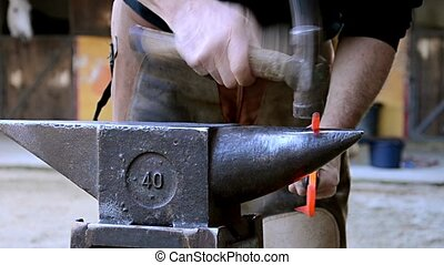 equine farrier at work - a farrier forging a horseshoe