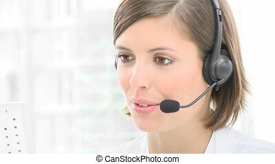 Close-up of smiling woman working in a call center. Customer...