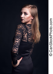 Woman in cocktail dress on black background