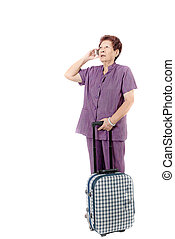 Asian senior woman talking mobile phone with suitcase...