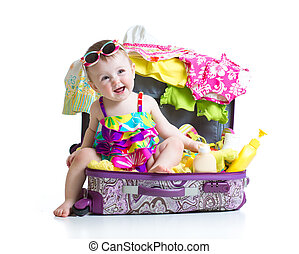 Child girl sitting in suitcase with things for vacation travel