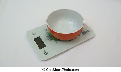 Digital kitchen scale and a bowl with sugar