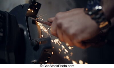 Close up the hands of a sharpening  axe on an electrical grinder beautiful sparks