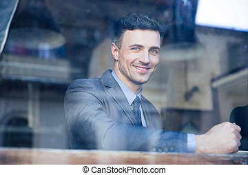 Portrait of a cheerful businessman in cafe