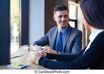 Smiling businessman and businesswoman talking in cafe -...