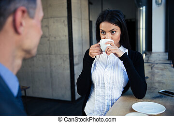 Businesswoman and businessman drinking coffee in cafe