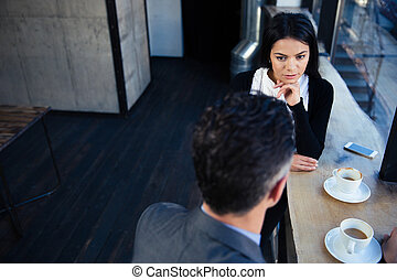 Businesswoman and businessman having coffee break and...