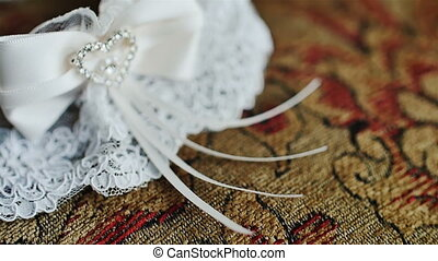 The garter of the bride laying on a pillow and prepared for...