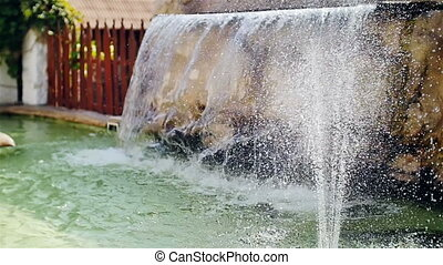 artificial waterfall with fountain in the garden slow motion