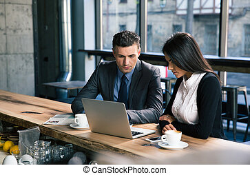 Businessman and businesswoman using laptop in cafe -...