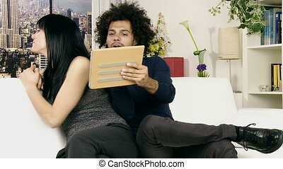 couple play with pillows on couch - happy couple playing...