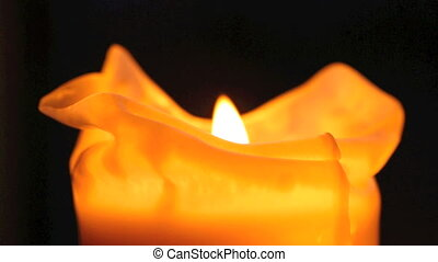 Burning candles in front of a dark background