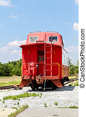 Red Caboose Under Blue Sky - An old red caboose on a track...