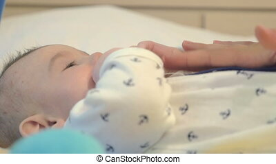Adorable newborn boy playing with h