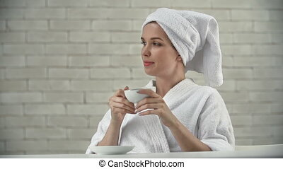 Pleasurable Day - Lady in bathrobe treating herself to a cup...