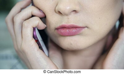 Phone Call - Extreme close up of female face talking on the...