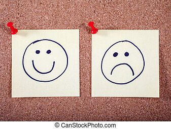 Happy and Sad Faces Pinned to a Noticeboard - A Happy and...