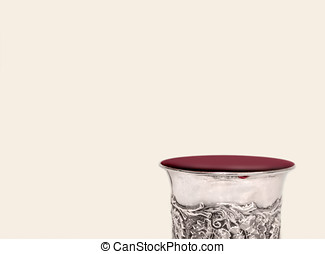 Shabbat silver kiddush cup overflowing with red wine close...
