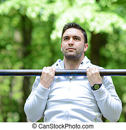 Crossfit man working out pull-ups on chin-up bar
