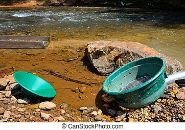 Gold panning in a river - Panning for gold in a river with a...