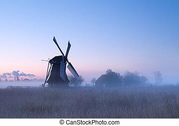 charming windmill in sunrise fog