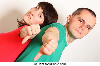Unhappy woman and man showing thumbs down - Unhappy and...