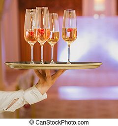 Waiter serving champagne on a tray - Waiter serving...