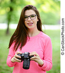 Beautiful female photographer outdoors holding camera