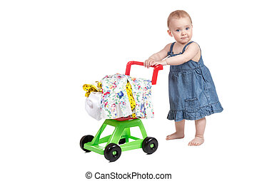 Child with a toy shopping trolley - Little girl in denim...