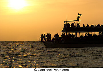 Ferry Boat Sihouette with passengers at sunset.