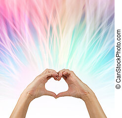 Sending love out - female hands making a heart shape with a...