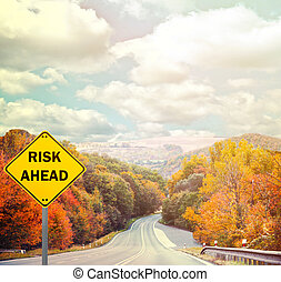"""RISK AHEAD"" sign against road - Business concept"