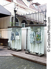 mannequins stand in storefront glass box