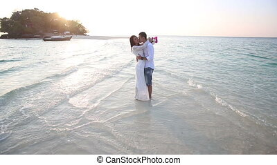bride and groom hug in water at spit against island -...